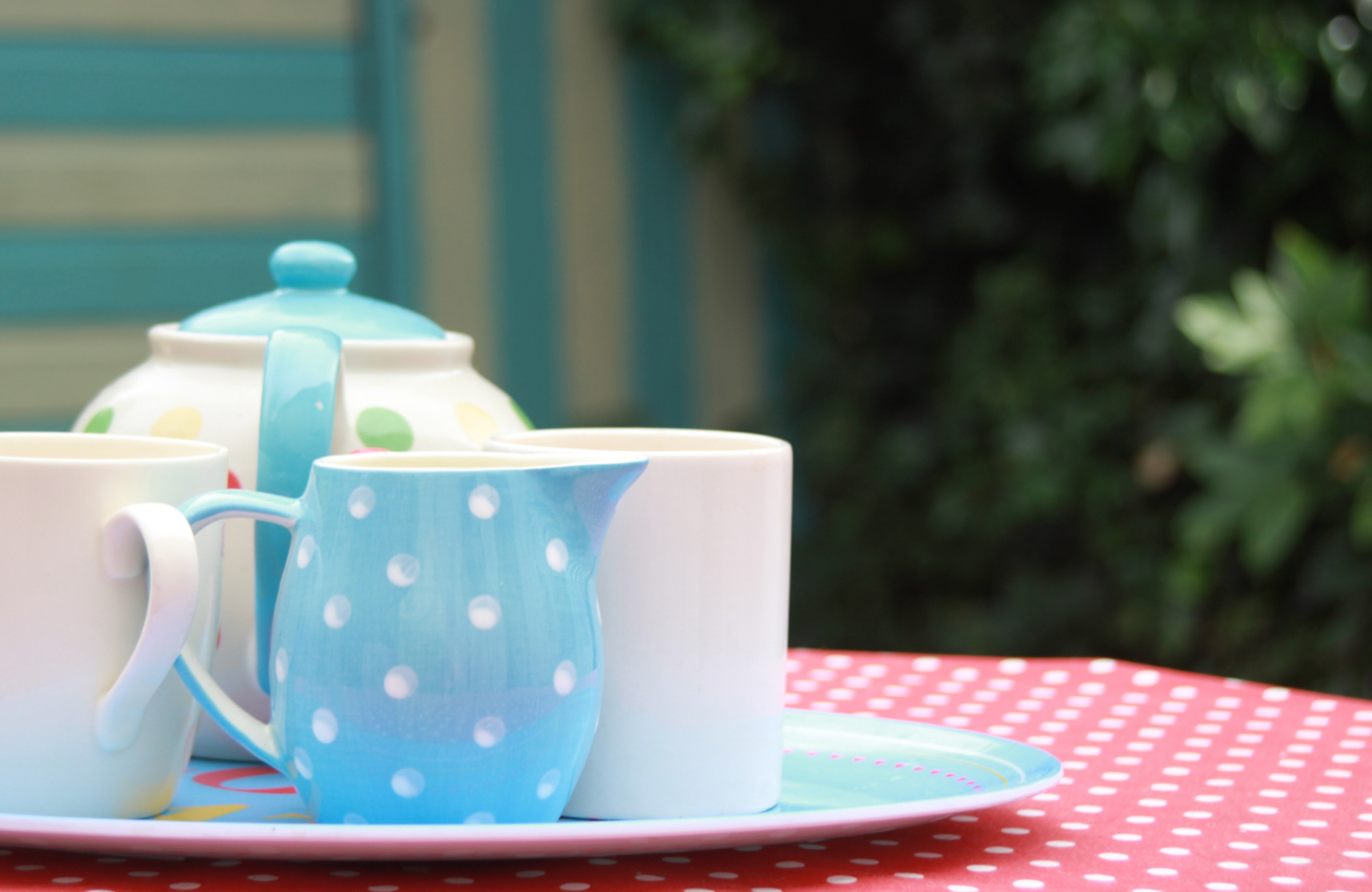 A tray on a table containing a teapot and mugs