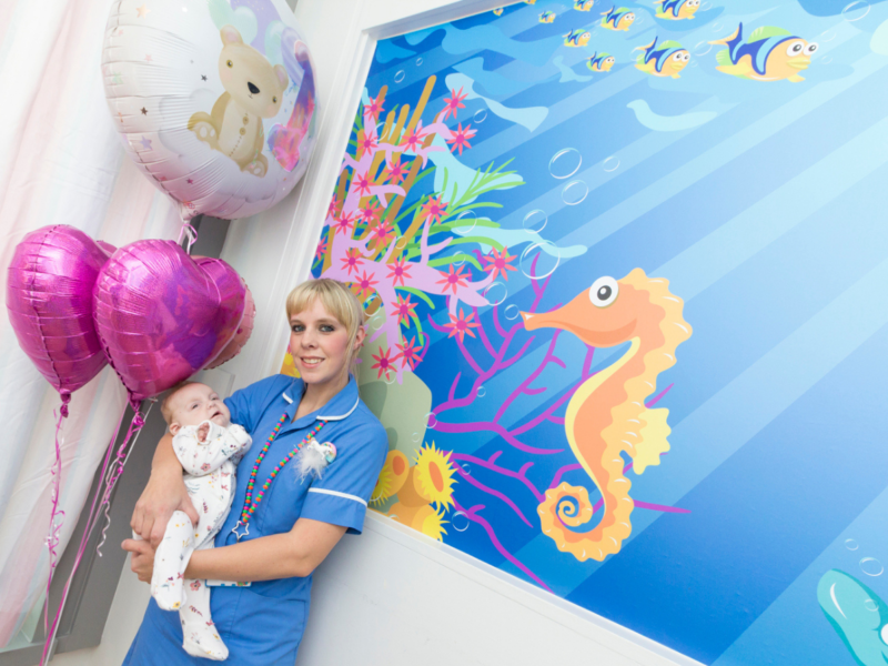 A nurse holds a baby in front of the a seahorse mural