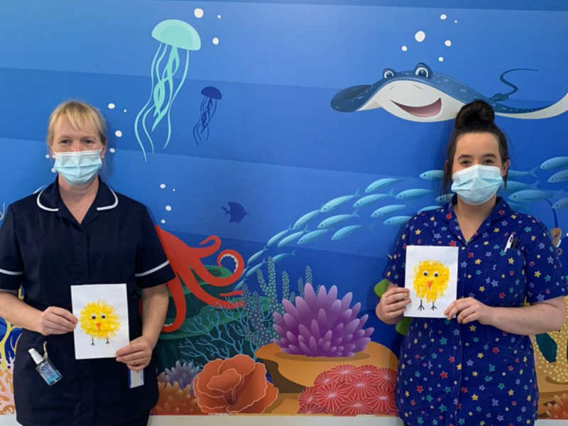Two paediatric nurses hold Easter cards