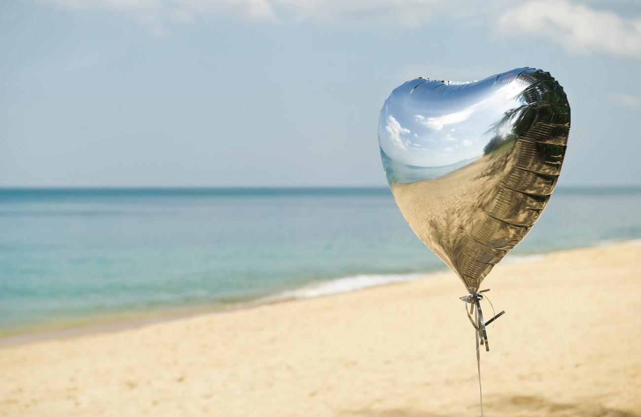 A single heart shaped balloon on a beach