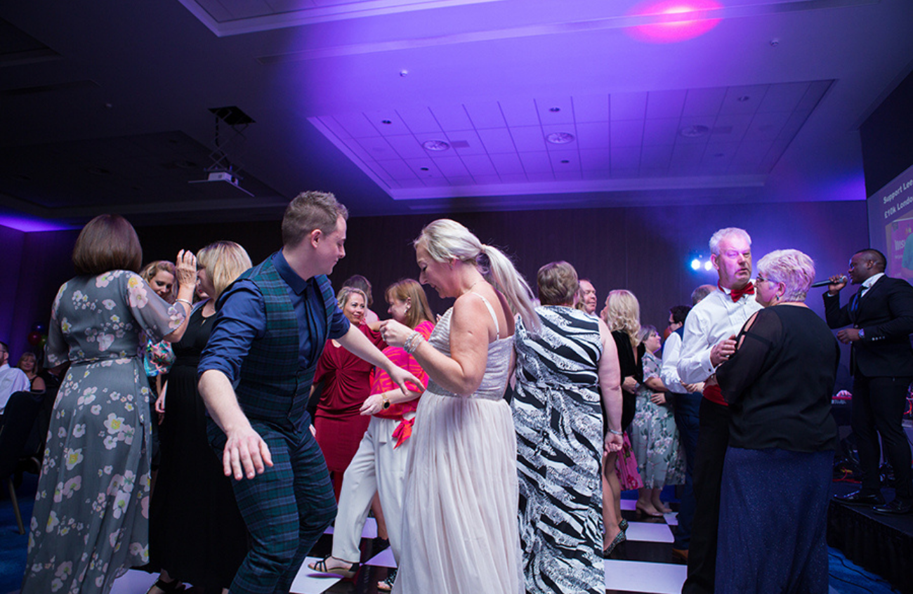 A group of people dance on a busy dance floor