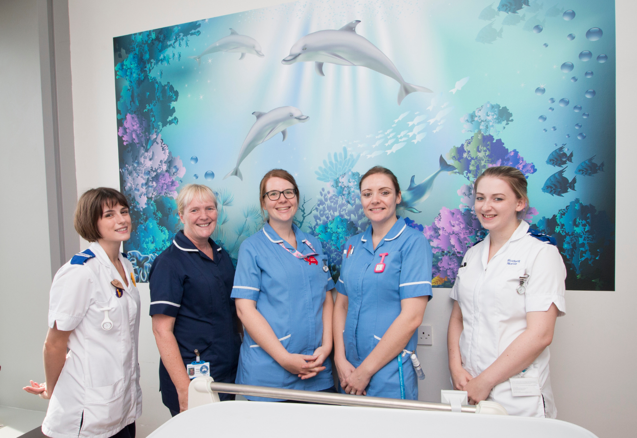 Ward staff in front of a dolphin themed wall