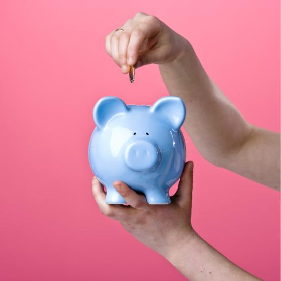 A person putting money into a piggy bank