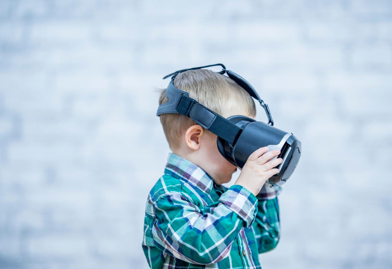 A little boy uses a virtual reality headset