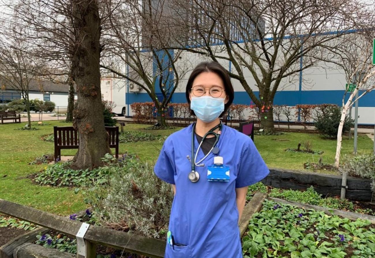 A member of staff wearing scrubs created by volunteers