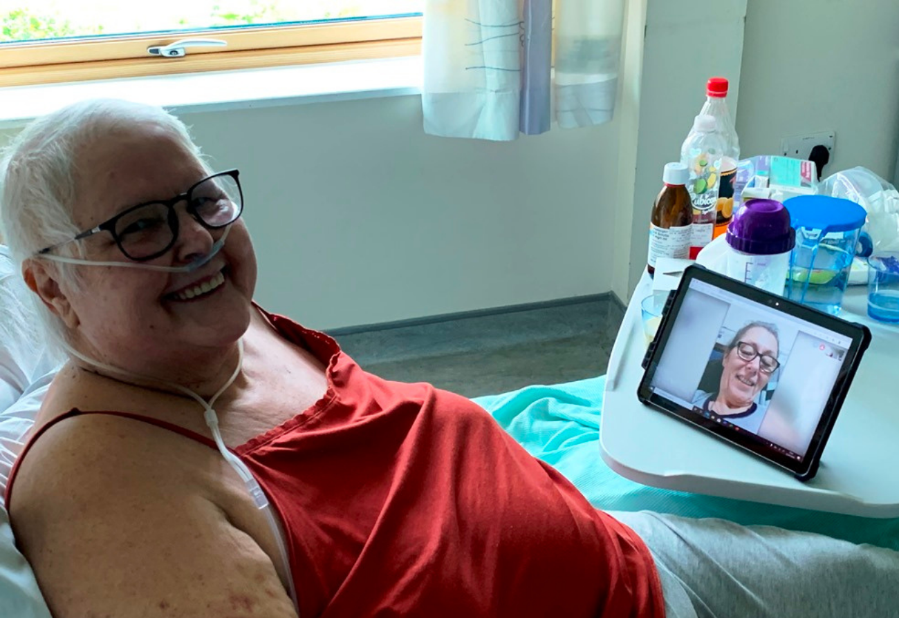 A patient talks a loved one using a tablet