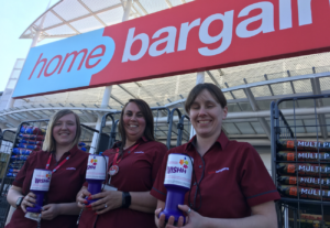 Home Bargains staff members hold WISHH Charity tubs